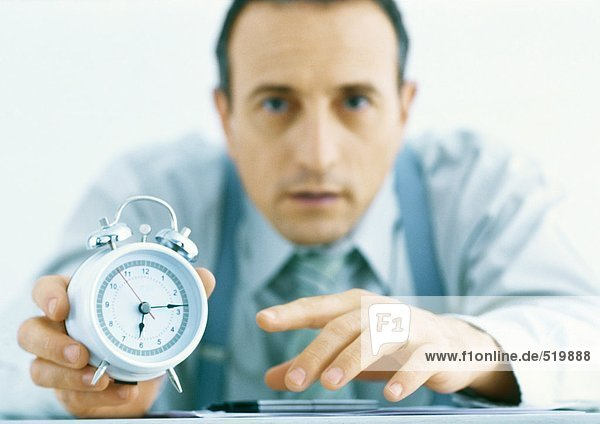 Mann mit Wecker  Zeiger und Uhr im Vordergrund
