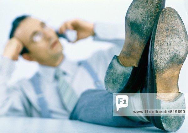 Mann am Telefon mit den Füßen auf dem Tisch  Fokus auf den Füßen im Vordergrund