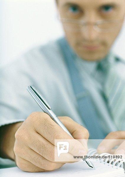 Mann schreibt mit Füllfederhalter