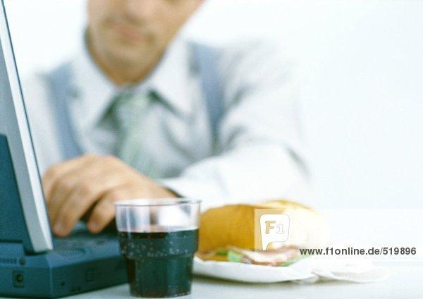 Mann mit Laptop und Essen  Fokus auf Getränk und Sandwich im Vordergrund