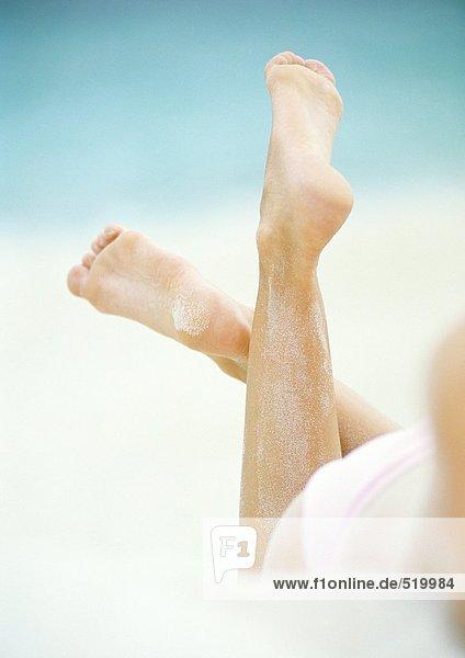 Frau im Sand liegend  Nahaufnahme der Unterschenkel