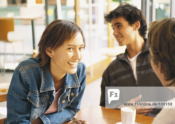 Group of young people sitting at table in café  smiling