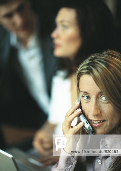 Businesswoman using cell phone in front of two co-workers