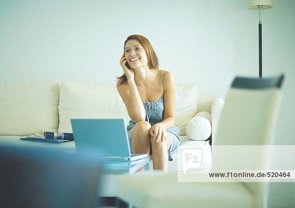 Frau mit Handy  auf der Couch sitzend