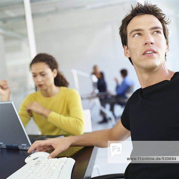 Lässig gekleidete Leute  die im Büro arbeiten.