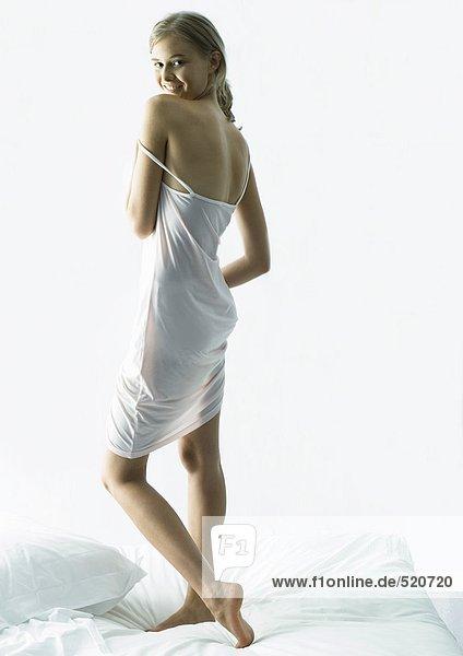 Junge Frau auf dem Bett stehend  über die Schulter schauend