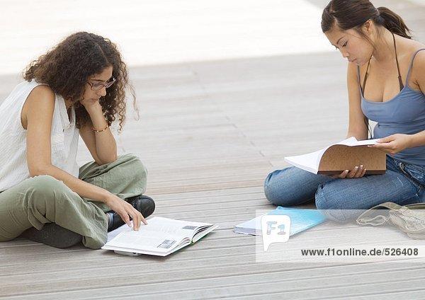 Zwei Studenten sitzen auf dem Boden und studieren
