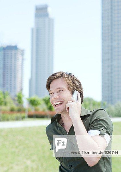 Junger Mann mit Handy im Stadtpark