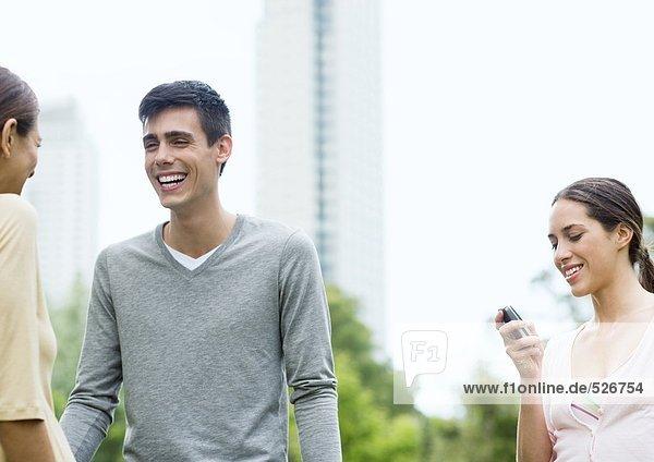 Junger Mann und zwei junge Frauen im Stadtpark