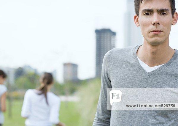 Junger Mann mit Stirnrunzeln im Stadtpark