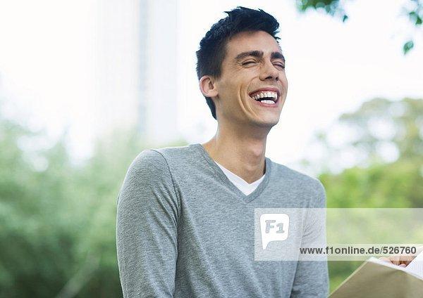 Junger Mann beim Lesen und Lachen im Stadtpark