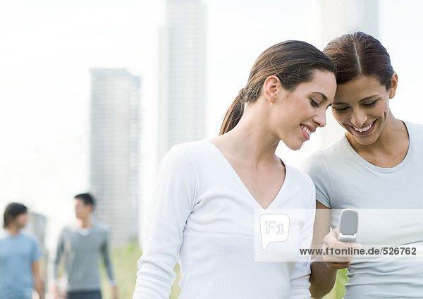 Zwei junge Frauen  die auf das Handy im Stadtpark schauen