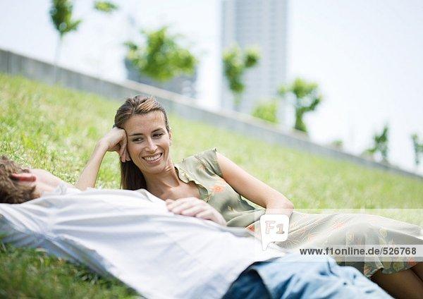 Junges Paar auf Gras im Stadtpark liegend