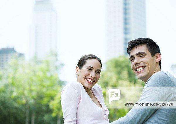 Junges Paar lächelt im Stadtpark