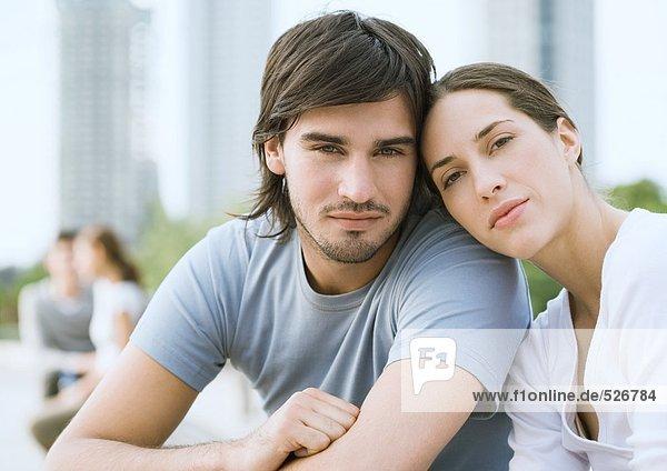 Junges Paar im Stadtpark  Frau ruht mit dem Kopf auf der Schulter des Mannes