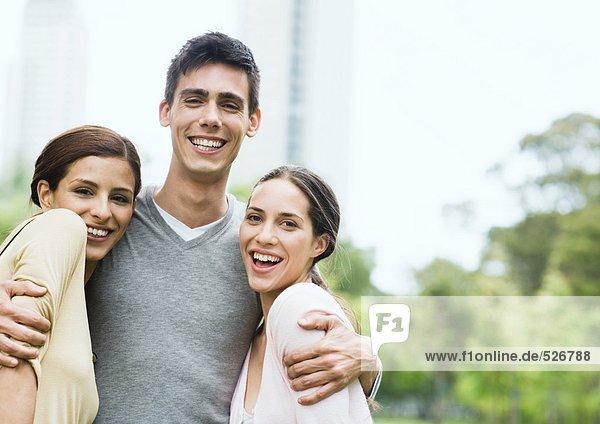 Junger Mann steht mit Armen um zwei junge Frauen im Stadtpark