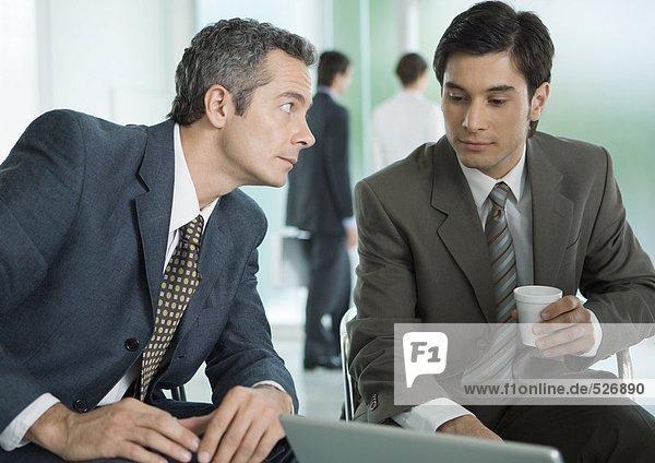 Zwei Geschäftsleute sitzen um den Laptop herum  einer mit Kaffeetasse