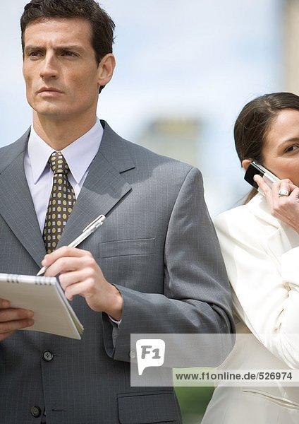 Geschäftsmann macht sich Notizen  während die Geschäftsfrau das Handy benutzt.