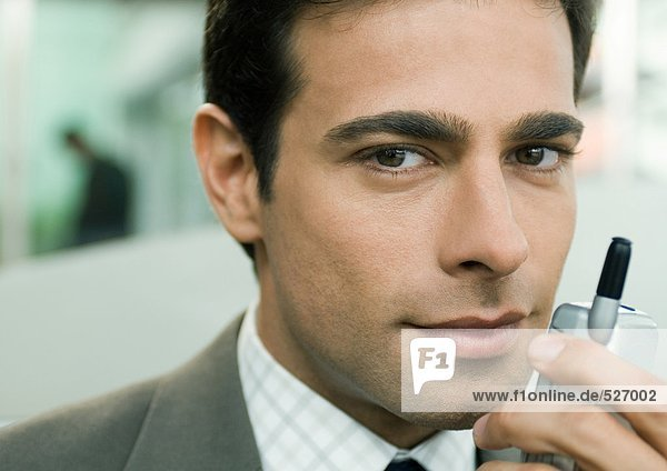 Businessman holding cell phone near face