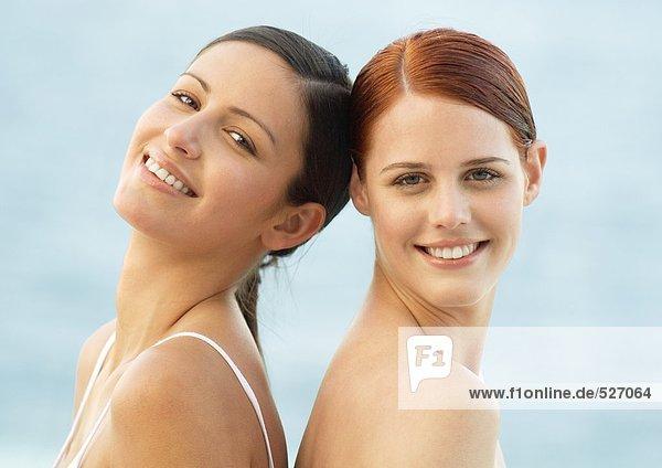 Zwei junge Frauen lächeln  Rücken an Rücken.
