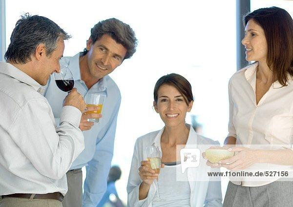 Reife Gruppe von Freunden  die vor dem Abendessen einen Drink zu sich nehmen.