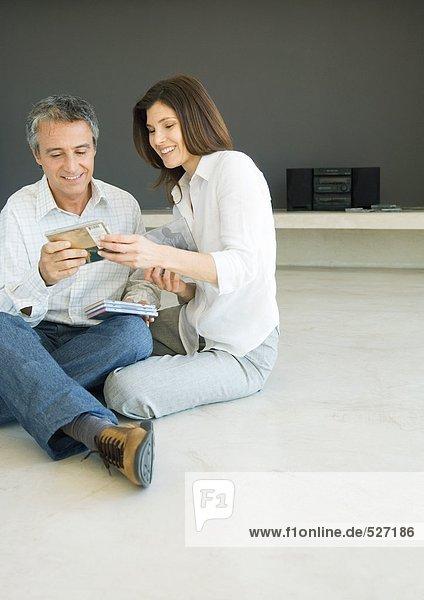 Ein reifes Paar sitzt auf dem Boden und schaut sich CDs an.