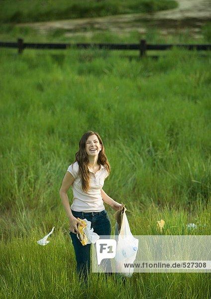 Frau sammelt Müll auf dem Feld ein.