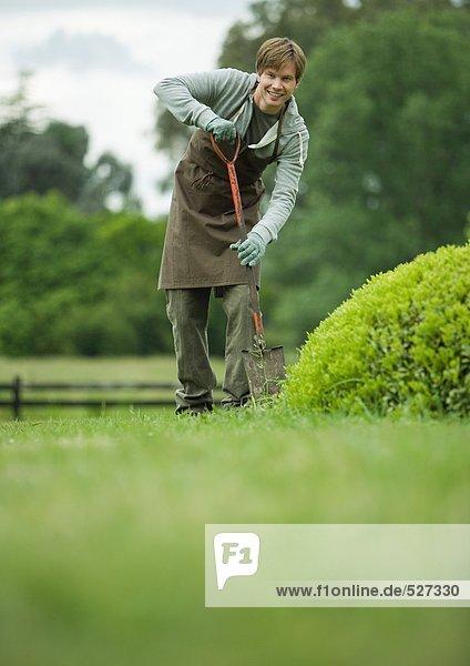 Junger Mann beim Graben im Hof