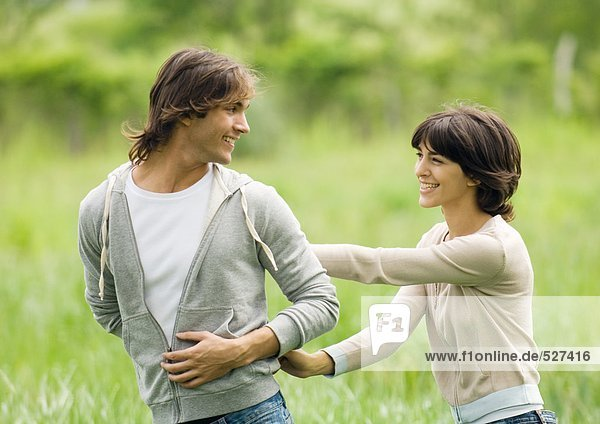 Junges Paar im Freien  Mann schaut Frau über die Schulter