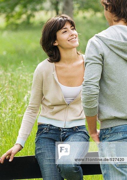 Junge Frau sitzt auf einem Holzzaun und schaut den jungen Mann an.