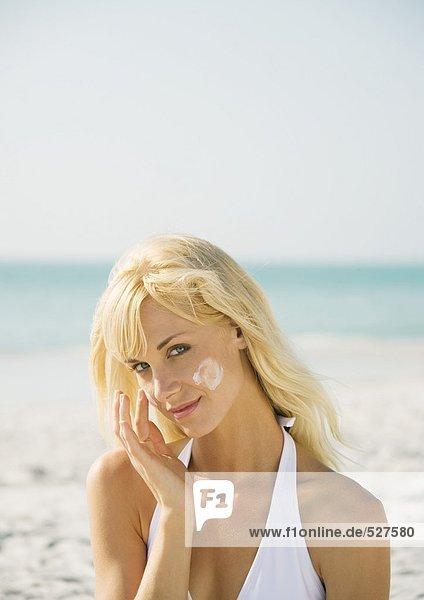 Frau  die Sonnencreme auf das Gesicht am Strand aufträgt.