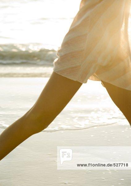 Frau beim Spaziergang am Strand  Mittelteil