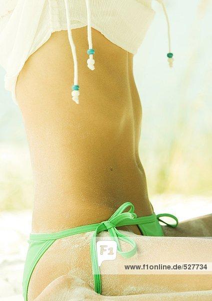 Frau im Bikini sitzend im Sand  Mittelteil