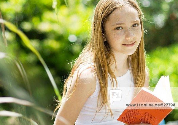 Mädchen mit Buch  lächelnd vor der Kamera