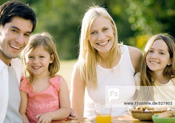 Familie sitzt am Tisch im Freien  lächelnd
