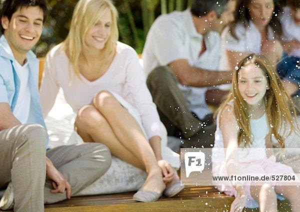 Mädchen spritzt Wasser  Familie entspannt im Hintergrund