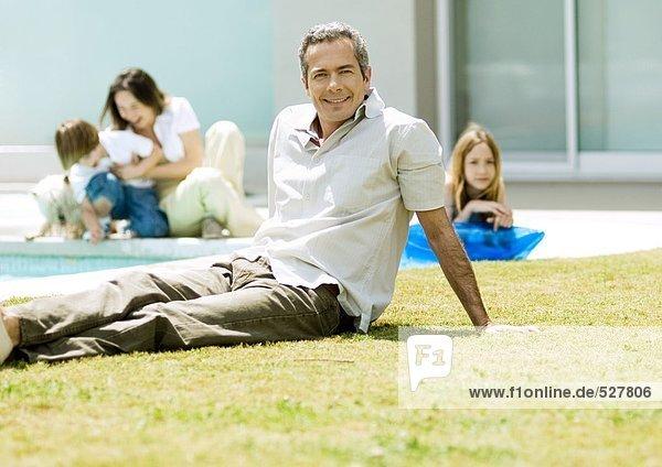 Mann entspannt auf Rasen  Familie im Hintergrund