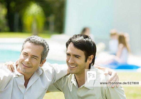 Zwei Männer mit Armen um die Schultern  lächelnd.