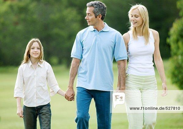 Mädchen beim Spaziergang mit den Eltern