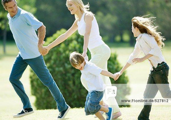 Familie beim Händchenhalten und Laufen