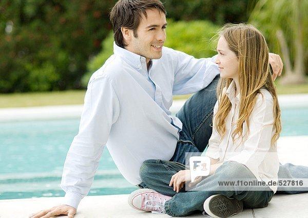 Vater und Tochter am Beckenrand sitzend