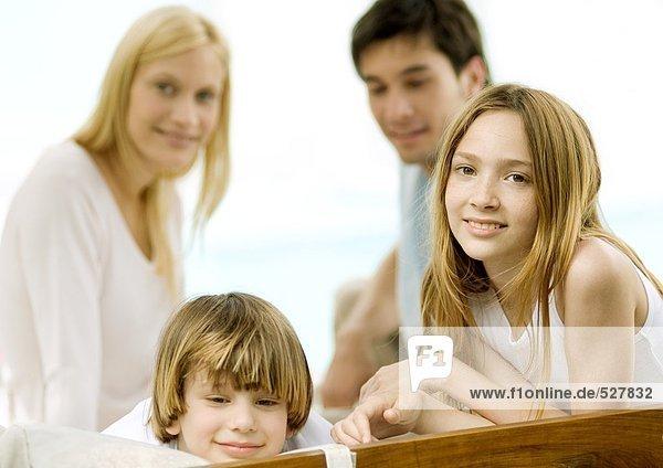 Junge und Mädchen  Eltern im Hintergrund