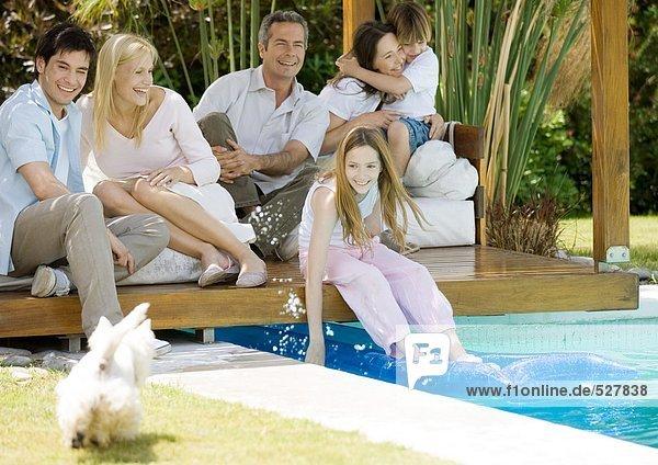 Großfamilie am Poolrand sitzend  Mädchen spritzt Wasser auf Hund
