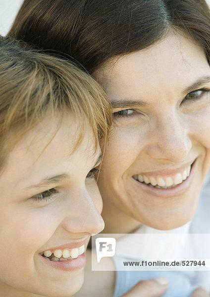 Mutter umarmt ihre Tochter  beide lächelnd  Nahaufnahme