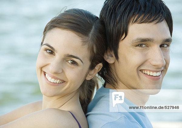 Junges Paar sitzend Rücken an Rücken am Wasser  beide lächelnd