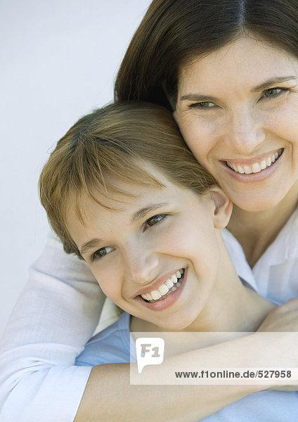 Mutter wilth Arm um die Schultern ihrer Tochter  beide weg schauend und lächelnd  Portrait  Nahaufnahme