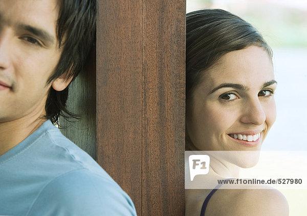 Junges Paar steht Rücken an Rücken mit einem Holzpfosten dazwischen  lächelnd  Portrait  Teilansicht