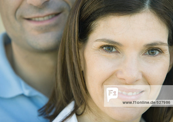 Woman smiling and looking at camera with her husband behind her  portrait  extreme close-up