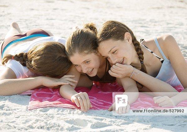 Three preteen girls lying on beach and giggling