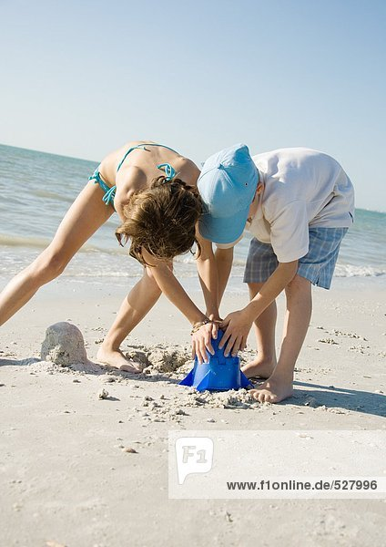 Boy and girl building sand castle together on beach